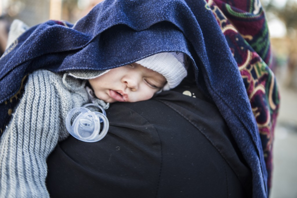 Amir Mahdi, 5 month olf from Afghanistan sleeps on her mum's shoulder in Moria Camp. Nov 18, 2015